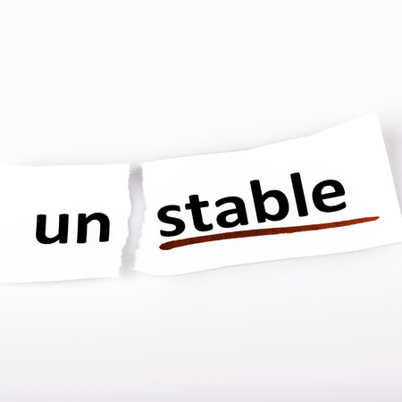 unstable: The word stable changed to unstable on torn paper and white background Stock Photo