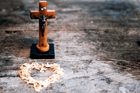 yellow heart: Beautiful old cross with jesus and yellow heart from leafs on the old wooden floor