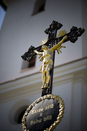 closer: black cross with gold jesus and chapel as background with czech text through cross closer to god Stock Photo