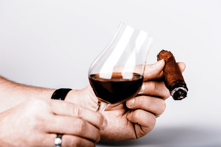 Old brandy or rum in glass and cigar in male hand on white background photo