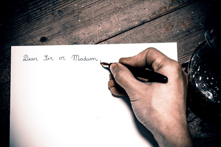 addressing: Old fashioned letter with a pen in a hand Stock Photo