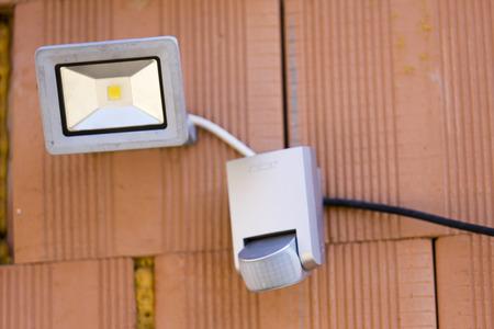 La sécurité a mené la lumière avec une cellule de détection de mouvement ou capteur sur le mur de la maison Banque d'images - 39565572