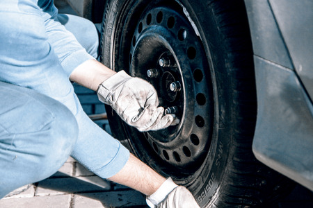 car mechanic: Changing tires or wheel before winter or spring