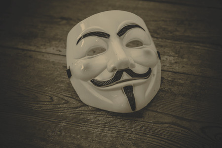 vendetta: white anonymous mask on wood background - retro style