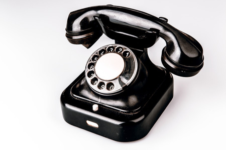 Old black phone with dust and scratches, isolated on white background - retro Stock Photo