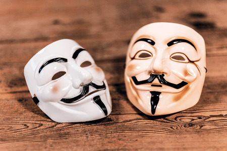 guy fawkes: white and yellow anonymous masks on wood background - retro style Stock Photo