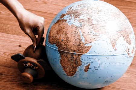 coin box: Pig money box with hand with coin and globe. Pig is staring at globe. Stock Photo