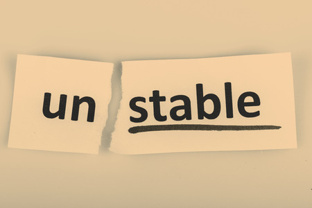 steadiness: The word stable changed to unstable on torn paper and white background Stock Photo