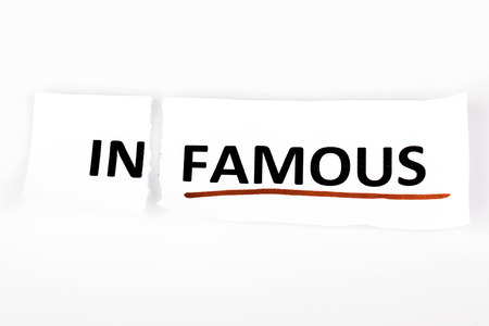 infamous: The word infamous changed to famous on torn paper and white background