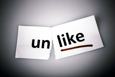 unlike: The word unlike changed to like on torn paper and white background