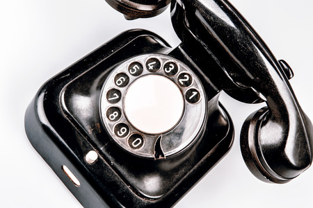 phone cord: Old black phone with dust and scratches, isolated on white background - retro Stock Photo