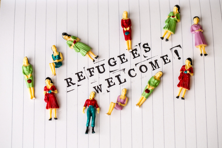 amnesty: refugees welcome text on white line paper with woman figures around Stock Photo