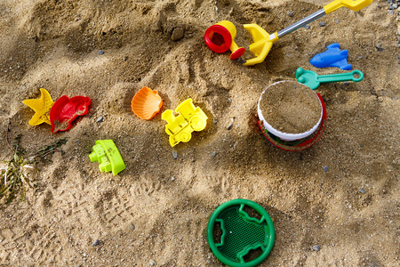 children toys on sand or beach - yeallow, red, blue, green Stock Photo