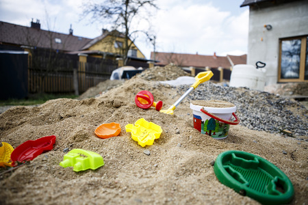 children toys on sand  - yeallow, red, blue, green Stock Photo