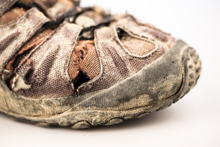 sport shoe: detail of old damaged hike shoe on white background