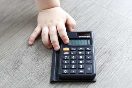 calc: black calculator on old wooden floor with child hand