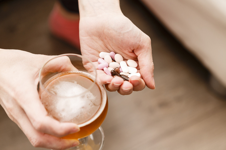 sleeping pills: addict problem, woman with pills and beer in hands. drugs and narcotics