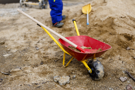 child in blue work pants play with sand, red shovel and small barrow