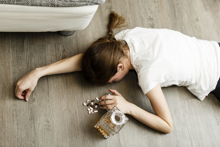 drunk or poisoned young woman with bottle of alcohol and pills, whisky and drugs, addiction Stock Photo