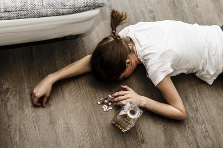 Betrunken oder vergiftet junge Frau mit einer Flasche Alkohol und Pillen, Whisky und Drogen, Sucht Standard-Bild - 77355999