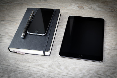 black calendar or diary with pen, smarthphone and tablet on wooden table, cellphone, floor