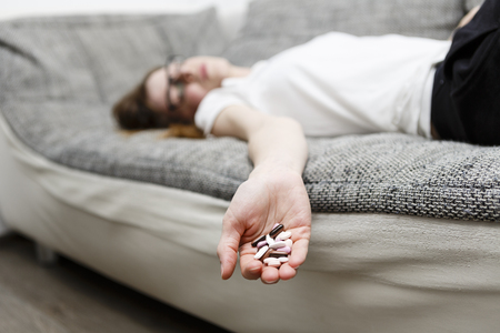 dead woman lie on sofa after she eat drugs or pills, addiction on medicine