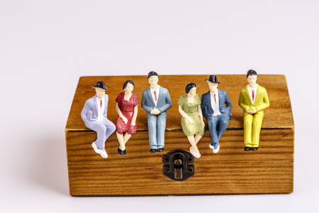 toy models of people sitting on the wooden box on white