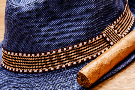 blue hat and cigar on wooden floor, smoke relax concept Stock Photo