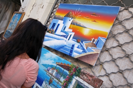 rethymno: RETHYMNO, GREECE - SEPTEMBER 11: Girl watching at picture in city Rethymno on September 11, 2013 in Rethymno