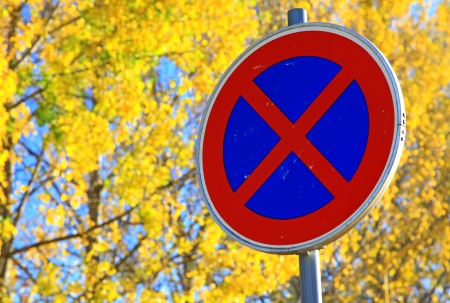 Road sign STOPPING and autumn trees photo
