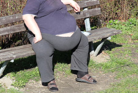 Obesity - fat man on a bench photo