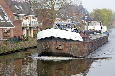dweling: DELFT, NETHERLANDS - APRIL 2: Ship in water canal in the centre of the city Delft on April 2, 2014 in Delft Editorial