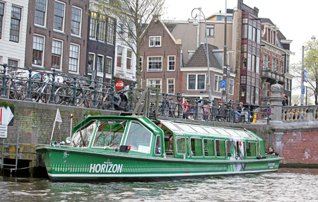 dweling: AMSTERDAM, NETHERLANDS - APRIL 3: Water canal and typical architecture in city Amsterdam on April 3, 2014 in Amsterdam