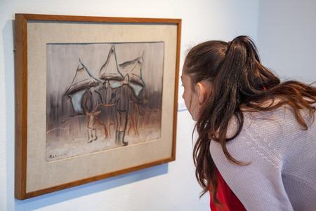 ruzomberok: RUZOMBEROK, ESLOVAQUIA - 22 DE JULIO: Muchacha que mira la pintura de Bazovsky en la galer�a de Ludovit Fulla el 22 de julio de 2014 en Ruzomberok Editorial