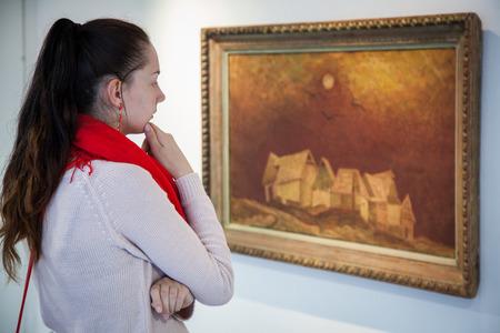ruzomberok: RUZOMBEROK, SLOVAKIA - JULY 22: Girl looking at Bazovskys painting in gallery of Ludovit Fulla on July 22, 2014 in Ruzomberok Editorial