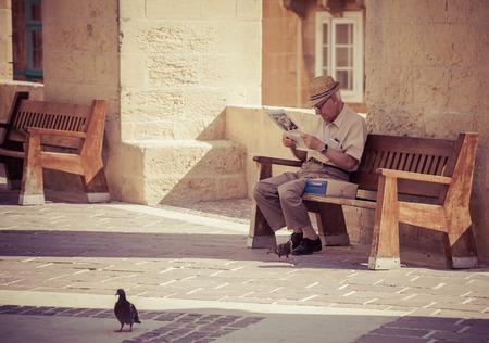 senior reading: VALLETTA, MALTA - JULY 17: Senior reading newspaper in Valletta on July 17, 2015 in Valletta Editorial