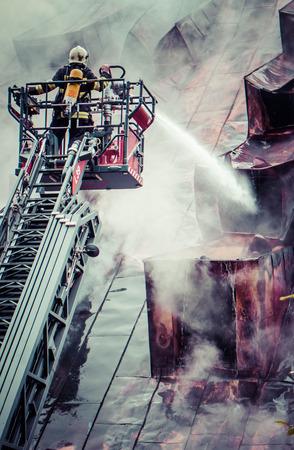 fireman: Fireman with hose on ladder Stock Photo