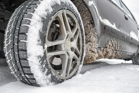pneumatic tyres: Detail of car. Tire standing on winter road with deep snow