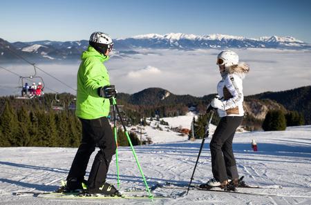 Skiërs op de helling bij skitoevlucht Malino Brdo, Slowakije. Inversielaag in vallei en Hoge Tatra met heuvel Krivan op backround.
