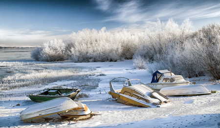 Boats on shore at lake Liptovska Mara, Slovakia covered in ice. Winter forest and blue sky