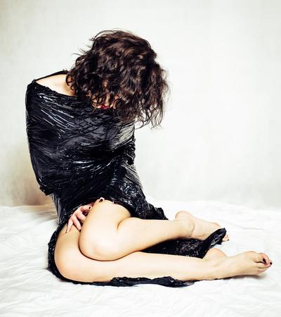 confined: Melancholy woman confined in black foil