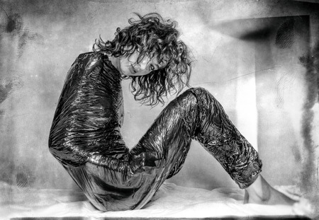 confined: woman confined in black foil Stock Photo