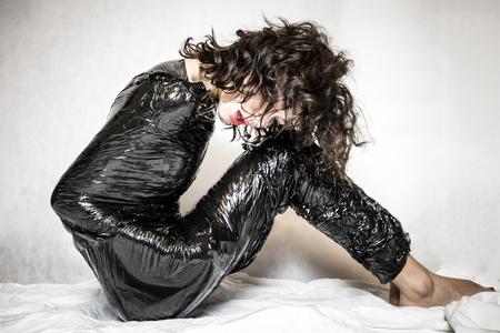 Pretty face woman confined in black foil Stock Photo