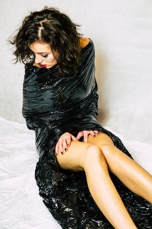 Pretty face melancholy woman confined in black foil
