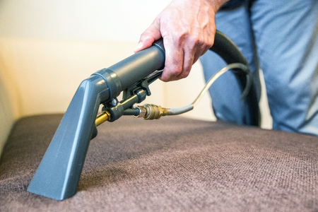 Cleaning couch with professional spray cleaner Stock Photo