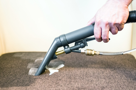 Cleaning couch with professional spray cleaner Archivio Fotografico