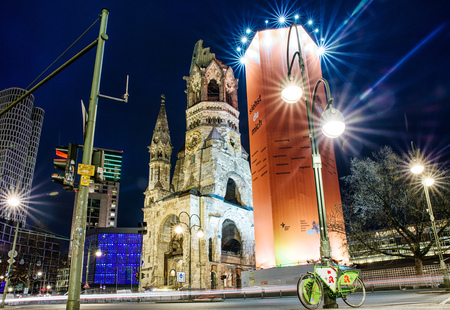BERLIN, GERMANY - APRIL 7: Bicycle under the lamp and ruins of Kaiser Wilhelm Memorial Church which was bombed during World war II on April 7, 2017 in Berlin Editorial
