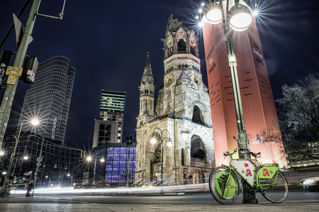 lighted: BERLIN, GERMANY - APRIL 7: Traffic and ruins of Kaiser Wilhelm Memorial Church which was bombed during World war II on April 7, 2017 in Berlin