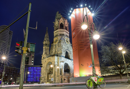 bombed city: BERLIN, GERMANY - APRIL 7: Bicycle under the lamp and ruins of Kaiser Wilhelm Memorial Church which was bombed during World war II on April 7, 2017 in Berlin Editorial
