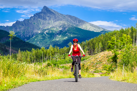 Happy woman on MTB bike on road in Ticha valley at High Tatras mountains, Slovakia.